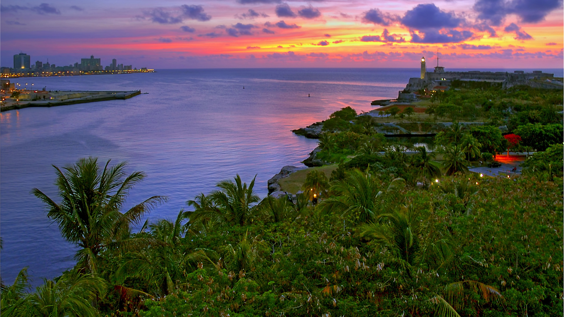 Cuba. Morro Castle and entrance to Havana Bay, seen from the La Cabaña at dusk. Beautiful tropical garden in the foreground.
