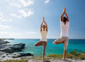 34811909 - fitness, sport, and lifestyle concept - couple making yoga exercises on beach from back